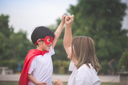 Asian Mother and her son playing together in the park,Asian Mother and her son playing together in the park,Boy in Superheros costume. Stock Photo