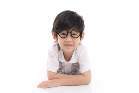 Cute asian boy wearing glasses lying on white background isolated Stock Photo