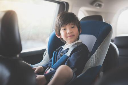 Portret van schattige Aziatische kind zit in autostoel Stockfoto