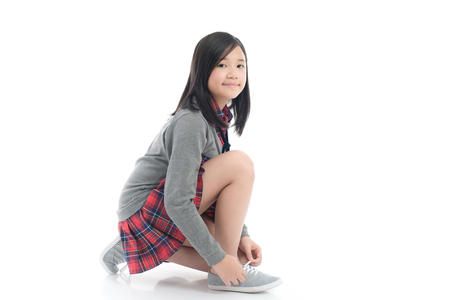 Beautiful asian girl tying shoelaces on white background isolated Stock Photo - 83616121