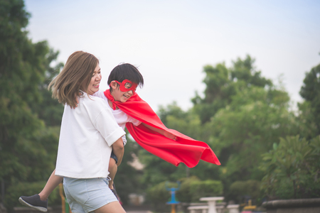 Asian Mother and her son playing together in the park,Boy in Superhero's costume. Stockfoto