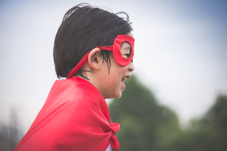 Asian child in in Superheros costume playing in the park Stock Photo