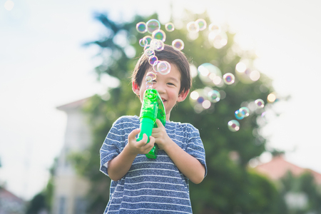 Cute Asian child Shooting Bubbles from Bubble Gun in the park