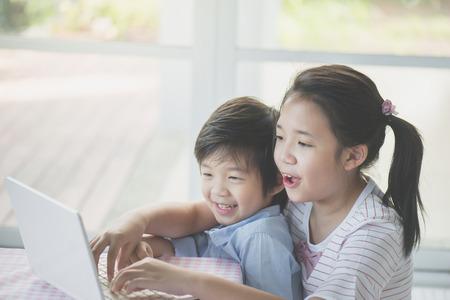 かわいいアジアの子どもたちが一緒にタブレットを使用して 写真素材