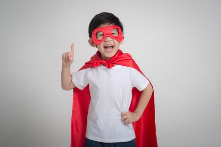 灰色の背景にスーパー ヒーローの衣装でのアジアの子供の肖像画