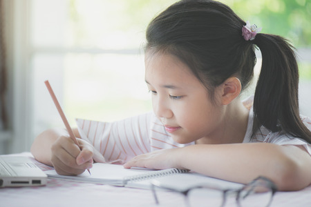 Beautiful asian girl writing to diary on the table Imagens
