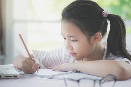 Beautiful asian girl writing to diary on the table Standard-Bild