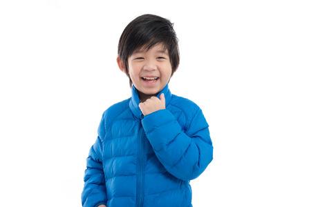 Gelukkig Aziatisch kind in blauwe winterkleren staande op witte achtergrond geïsoleerd