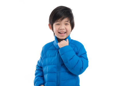 Happy asian child in  blue winter clothes standing on white background isolated Stock fotó