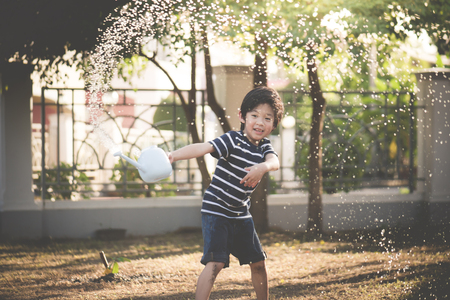 Cute Asian child watering in the garden on summer day Stock Photo