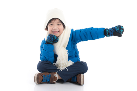 Happy asian child in  blue winter clothes sitting and pointing on white background isolated