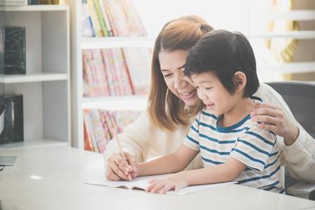 Madre asiática ayudando a su hijo a hacer la tarea en la mesa blanca