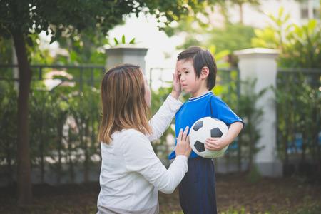 아시아 어머니와 아들 공원에서 함께 축구 재생 스톡 콘텐츠