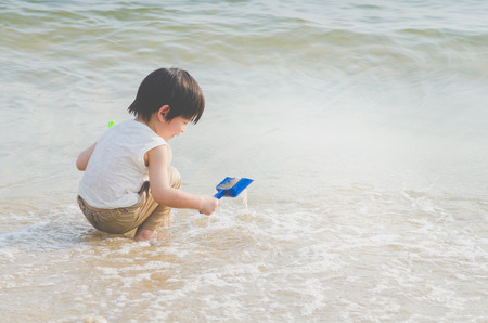Cute asian boy playing on the beach Фото со стока - 87489738