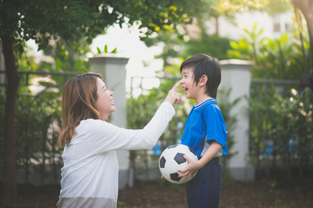 アジアの母と息子一緒に公園で遊ぶサッカー 写真素材