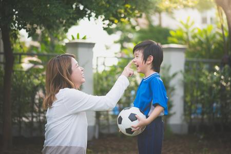 Aziatische moeder en zoon Spelen voetbal in het park samen Stockfoto