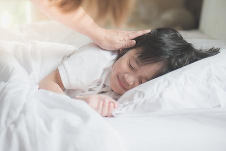 귀여운 아시아 어린이 어머니가 배려와 흰색 침대에서 자고
