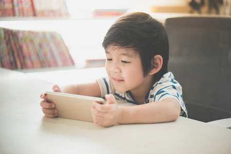 Happy Asian child using mobile phone on white table
