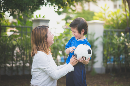 Asian mother and son Playing Soccer In Park Together