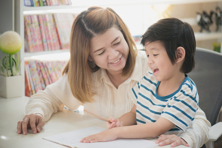 Asian mother helping her son doing homework on white table
