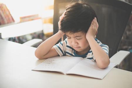 불행 한 아시아 아이 혼자 집에서 하드 숙제를 작업