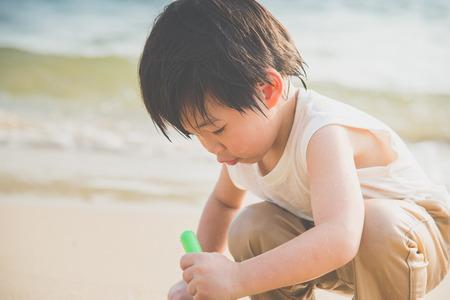 Cute asian boy playing on the beach Фото со стока - 87489798