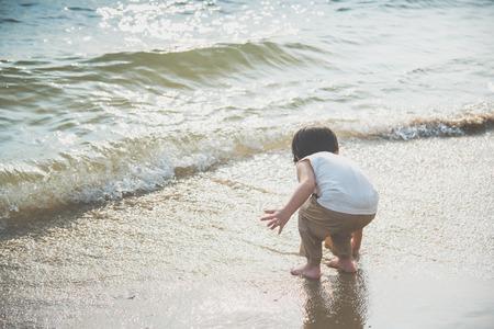 Back of Cute asian boy playing on the beach Фото со стока - 87489799