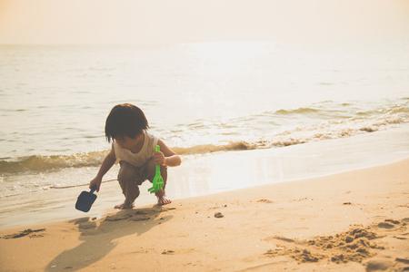 Cute asian boy playing on the beach Фото со стока - 87489810