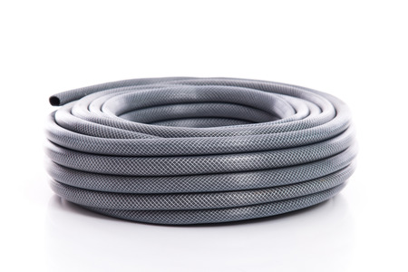 curled garden hose isolated on white background Фото со стока