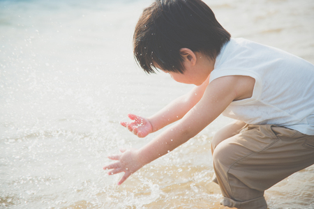 Cute asian boy playing on the beach Фото со стока - 87489818