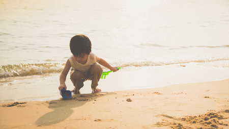 Cute asian boy playing on the beach
