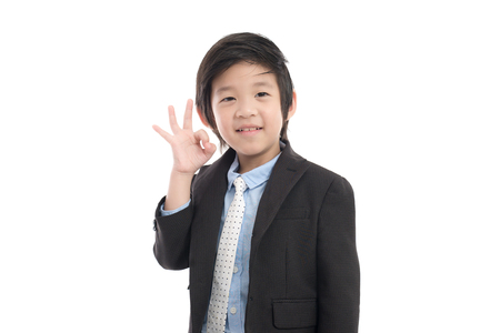 Asian child in business suit showing ok sign,white background isolated