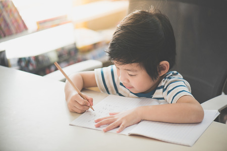 Little Asian child using a pencil to write on notebook at the desk