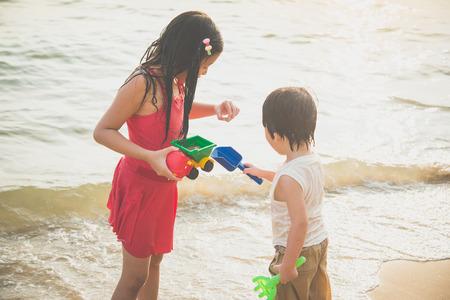 Cute asian children playing on the beach Фото со стока