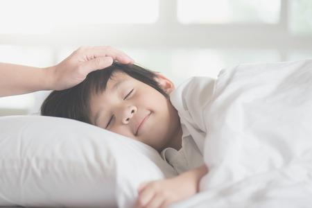 母親の世話で白いベッドで眠っているかわいいアジア子供