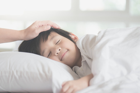 Cute Asian child sleeping on white bed with mother care