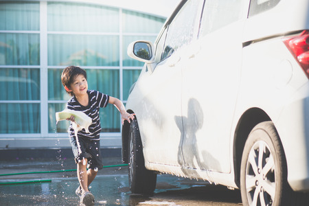 Cute asian child washing a car on summer day