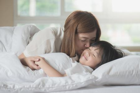 Asiatique mère embrassant son fils sur un lit blanc Banque d'images - 87907608
