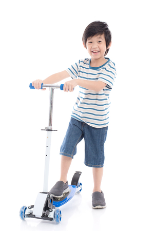 Cute Asian boy riding a scooter on white background isolated
