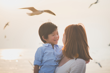 Happy Asian mother and son playing on the beach Фото со стока