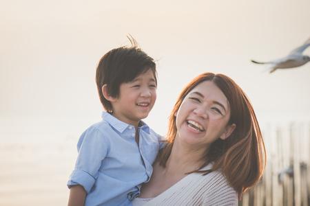 Feliz madre asiática e hijo jugando en la playa Foto de archivo - 89364779