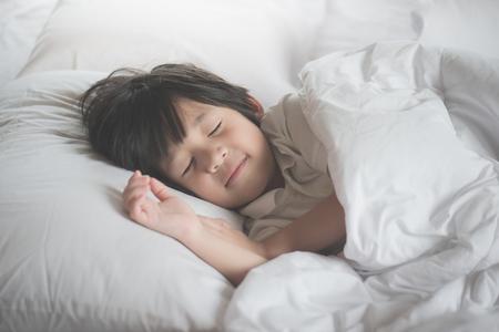 白いベッドで眠っているかわいいアジアの子供