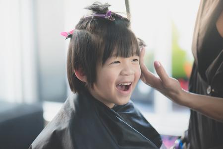 Cute Asian boy getting haircut at hairdresser salon