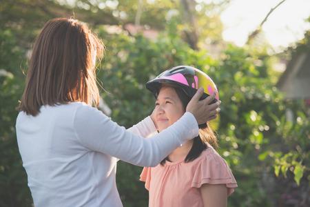 아시아 어머니가 딸에게 자전거 헬멧을 쓴다.