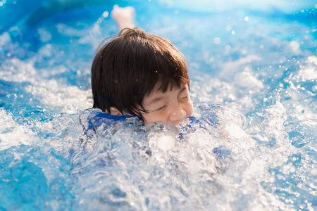 Cute Asian boy swimming and playing in a pool