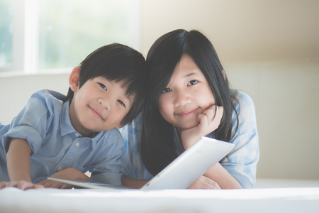 Cute Asian children  lying in bed and using laptop on white bed Stock Photo