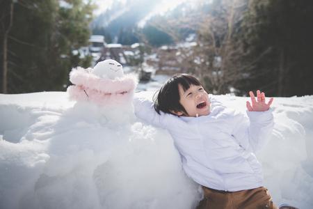 Little asian boy with snowman
