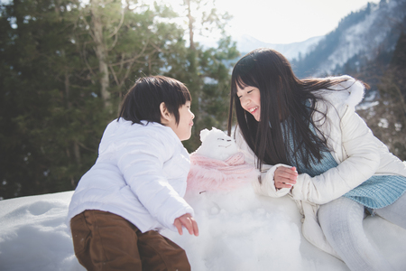 Cute Asian children playing with snowman