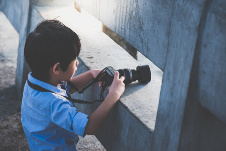 Cute Asian boy taking photo by digital camera outdoors Stock Photo