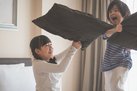 Happy Asian child ren having Pillow Fight in Hotel Room